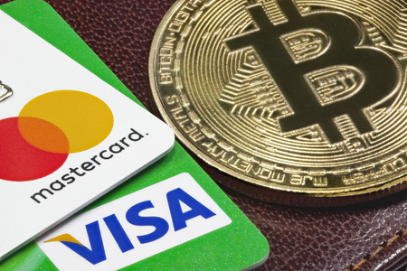 Visa, Mastercard credit cards  and golden bitcoin with the leather wallet on the background.