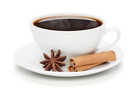 Taza blanca de café negro caliente con canela y anís estrellado, aislado en el fondo blanco, trazado de recorte incluido. Foto de archivo