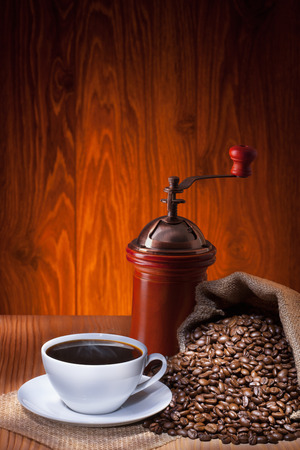 Cup of coffee with roasted beans and coffee grinder on wooden  background. Archivio Fotografico