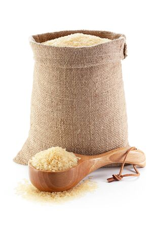 Rice in burlap sack and woodenware, isolated on the white background.