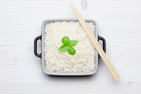 Rice with basil in ceramic bowl with chopsticks on white wooden table. Top view.