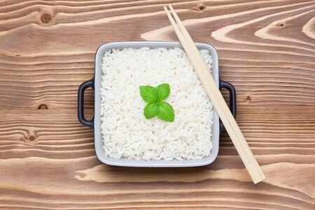 Rice with basil in ceramic bowl with chopsticks on wooden table. Top view.