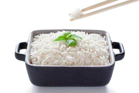 Rice with basil eaten from ceramic bowl with wooden chopsticks, isolated on the white background, clipping path included.