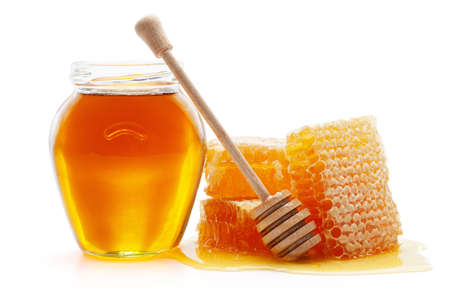 Honey in glass jar with wooden dipper and honeycombs, isolated on the white background, clipping path included. Archivio Fotografico