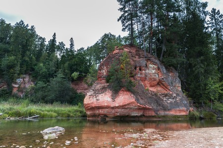 Summer landscape and red stone cliff of Zvartes in the basin of Amata river, Latvia, Europe. Daytime.