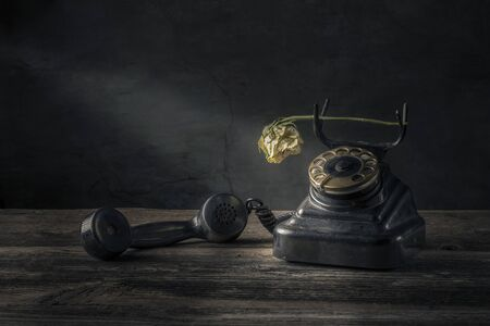 Vintage black phone on old wooden table background