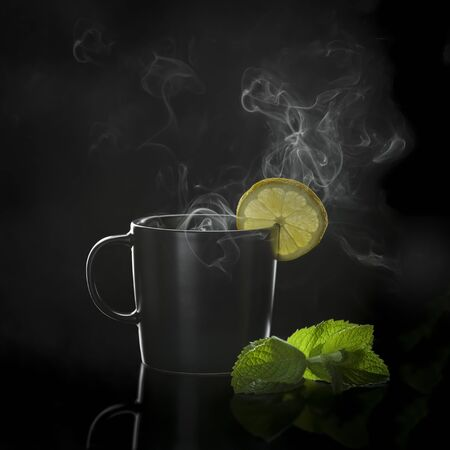 Tea in cup with leaf mint and lemon on black background
