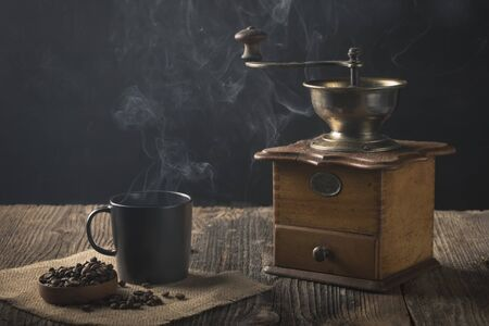 Antique coffee grinder with steaming coffee, and coffee beans Archivio Fotografico - 138026664