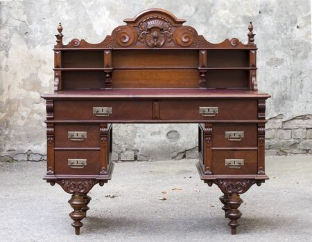 Antique wooden mahogany writing desk with wood carvings and turning Archivio Fotografico - 137414349