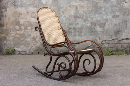 Old vintage dark brown rocking chair on a grey background