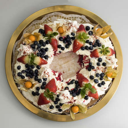 Delicious pavlova cake wreath of french meringue and whipped cream, decorated with strawberry, blueberries and physalis, cape gooseberry, view from above Archivio Fotografico