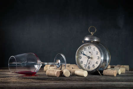 Empty wine glass of alcoholic drink, corks and vintage alarm clock, concept of alcoholism and alcohol abuse, dark table, gray background, can be used as a background