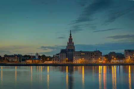Night view on the illuminated riverside with reflection on the river in Riga, Latvia Archivio Fotografico