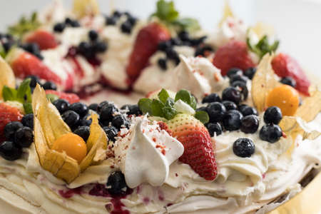 Delicious pavlova cake wreath of french meringue and whipped cream, decorated with strawberry, blueberries and physalis, cape gooseberry Archivio Fotografico