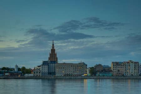 Night view on the illuminated riverside with reflection on the river in Riga, Latvia Stockfoto