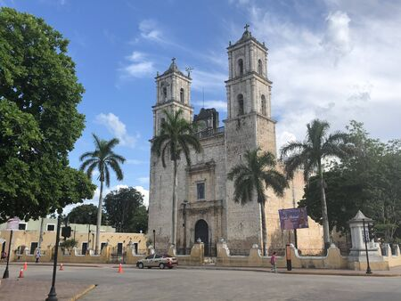 Church with palm trees in a blue sky with clouds in Valladolid, Yucatan, Mexico