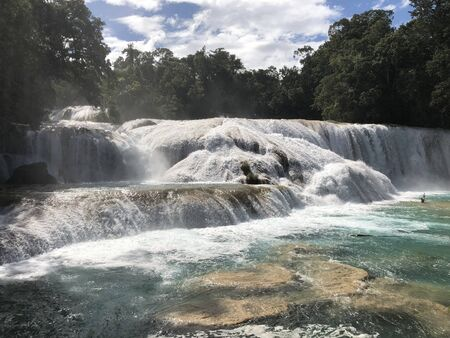 Agua Azul waterfalls with a cloudy sky, trees and rocks in Chiapas Mexico