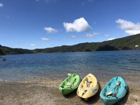 kayaks in lagunas de montebello in Chiapas, Mexico with hills at the back and a blue sky with clouds