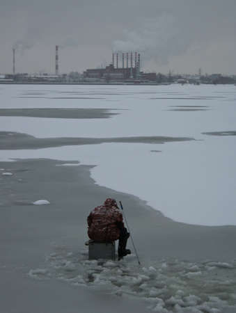 The fisherman fishes on ice of a reservoir against factory Stock Photo