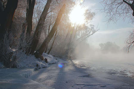 winter river in the freezing weather in the mist with the sun photo
