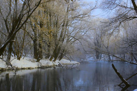 the river in early spring morning, surrounded by snow-covered trees Stock Photo