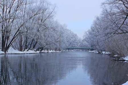 view of the spring river early in the morning in the shadow of snow-covered trees Stock Photo