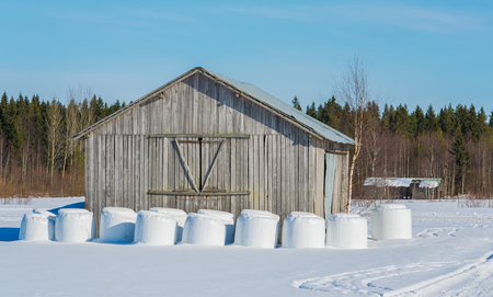 barns winter: Hay bales on the side of a barn in winter Stock Photo