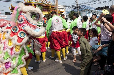 Nakhon Sawan, Thailand - February 6,2011 -  acrobatic lion dancer and boy look each other in chinese new year celebration