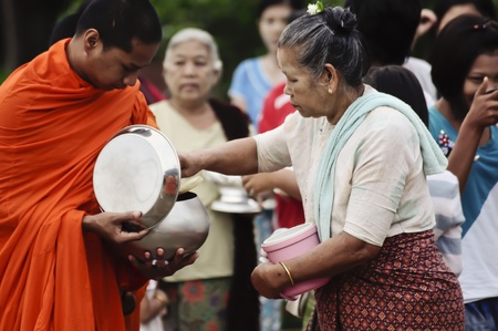 Sangklaburi, Thailand - May 11,2010 - Give food offerings to a Buddhist monk Editorial