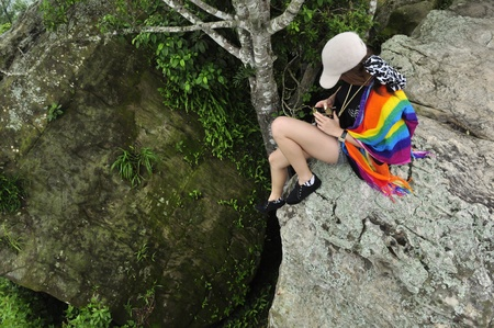 Asian teenager playing telephone on the cliff Stock Photo - 10061284