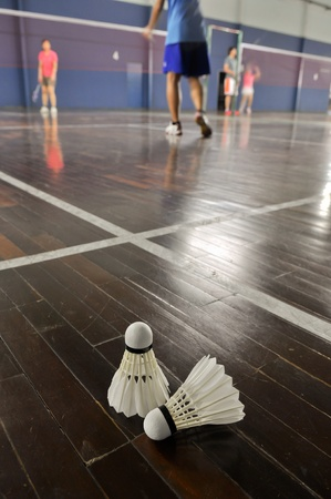 badminton racket: Badminton - two shuttlecocks in the badminton courts with players competing