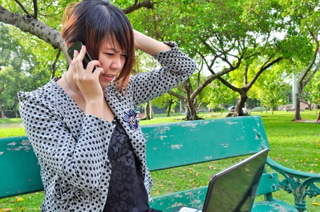 A stressed woman talk mobile phone with laptop in nature photo