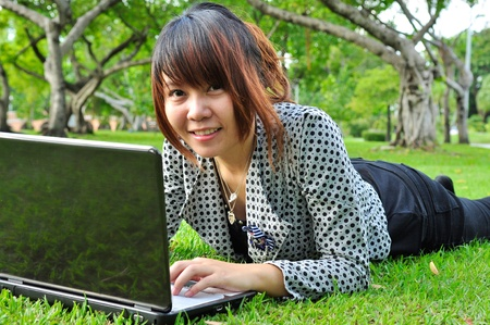 Smiling woman with laptop in nature photo