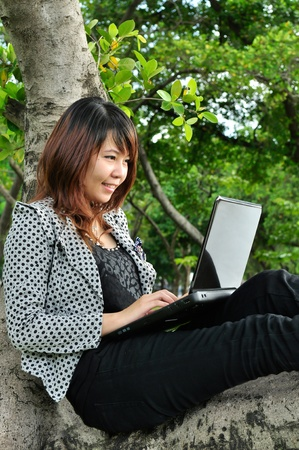 Portrait of beautiful woman smiling on the tree and playing laptop Stock Photo - 10669781