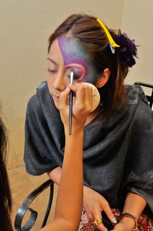 A beautiful young woman having the final touches applied to her make up by beautician photo