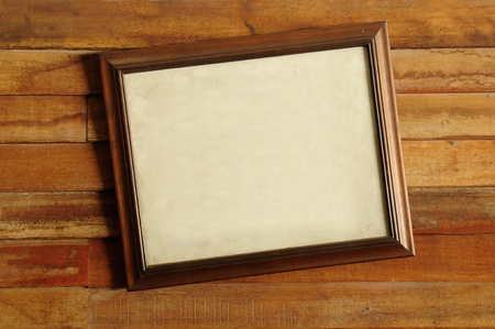Vintage wooden picture frame on the old wooden wall photo