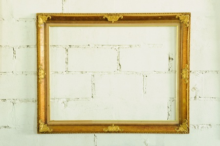 Vintage gold picture frame on white wall photo