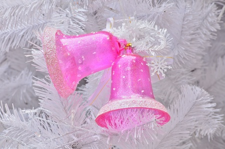 Pink jingle bell on Christmas tree photo