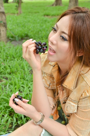 Beautiful woman eat fruit in the park Stock Photo - 13208378