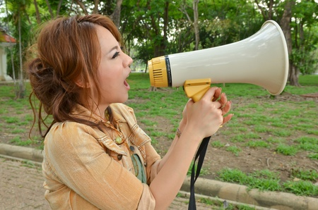 Beautiful woman yelling into megaphone in the park photo