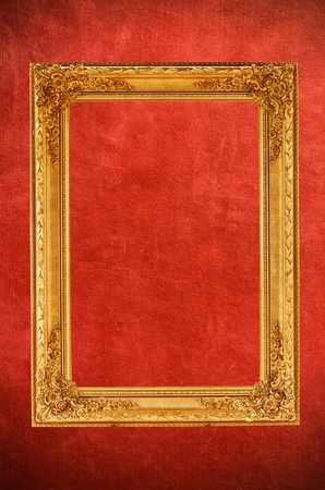 Vintage gold picture frame on vintage red background photo