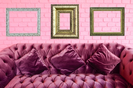 Vintage violet sofa and vintage picture frame on pink brick wall photo