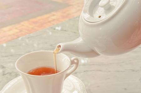 tea pouring into glass tea cup photo