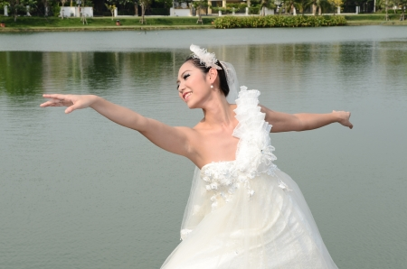 Beautiful girl in white gown of the bride dance photo