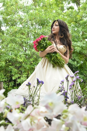 Beautiful woman with bouquet of pink rose standing in a beautiful flower garden and looking into the distance photo