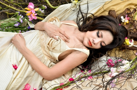 Young beautiful woman sleeping with flowers outdoor photo