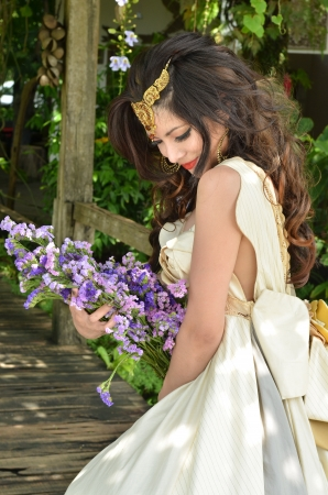 Beautiful woman with bouquet of flower standing in a beautiful garden