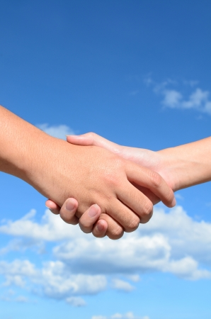Hand shake between a man and a woman on blue sky background Standard-Bild