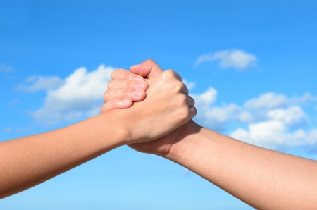 Partner hand between a man and a woman on blue sky background
