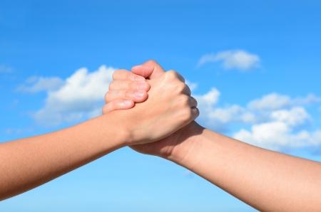 pacto: Socio mano entre un hombre y una mujer sobre fondo de cielo azul Foto de archivo